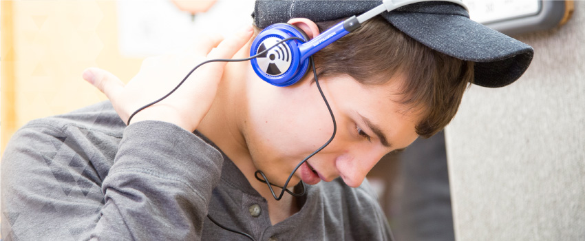 A young man listens to music using blue headphones.