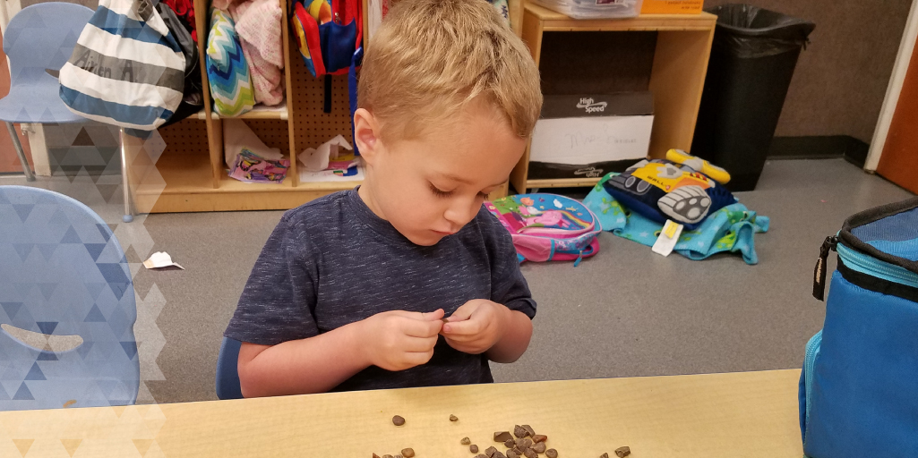 Brantley plays with some of the stones he enjoys collecting from the playground.
