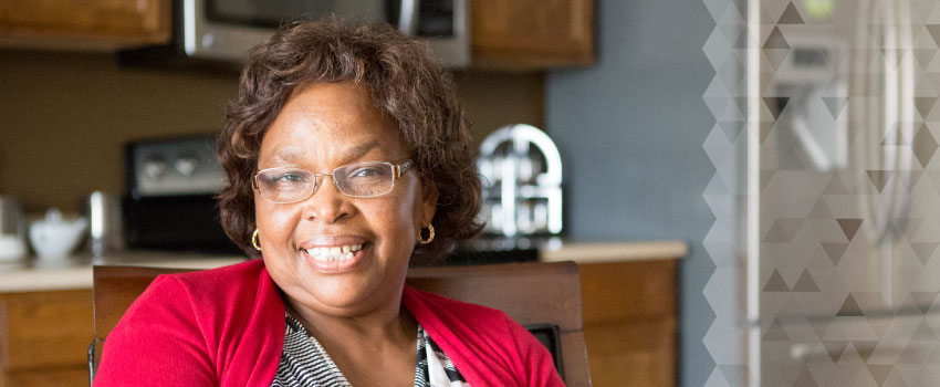 An African-American woman with glasses smiles in her kitchen.