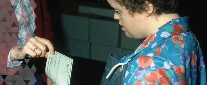 A young woman looks at her paycheck.