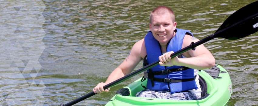 A young man paddles in a kayak on a lake. He is smiling.